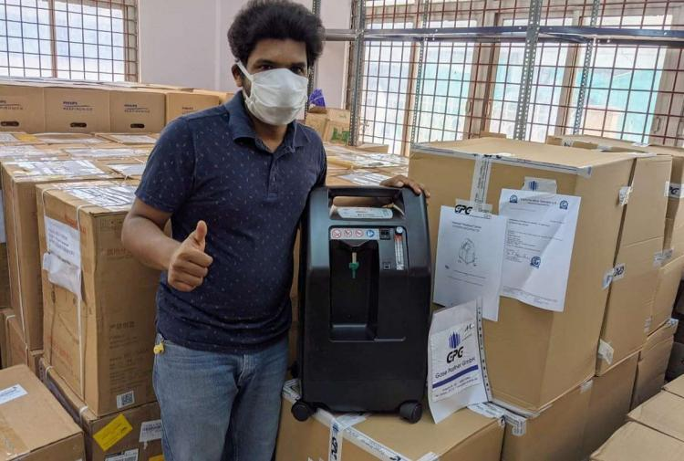 A man standing with cardboard boxes containing oxygen concentrators