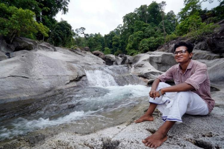 Vinod frost researcher from the Cholainaikkan Community sits on a rock near a natural waterfalls