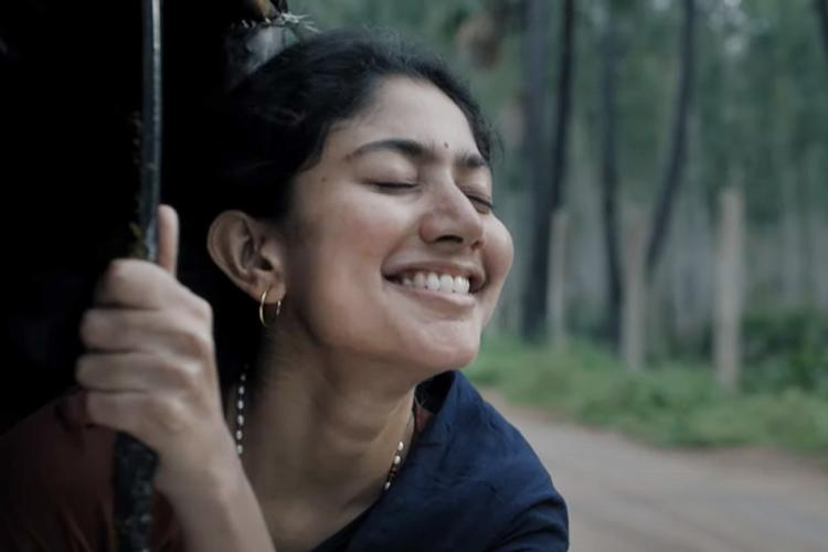 Sai Pallavi smiling and with her head hanging out from the side of an auto while holding on to a pole