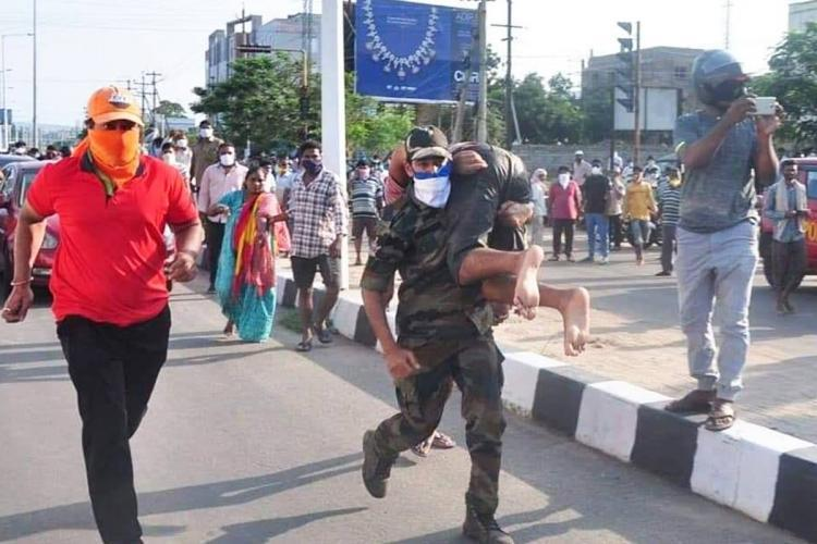 A police personnel carrying an unconscious man and running to save him