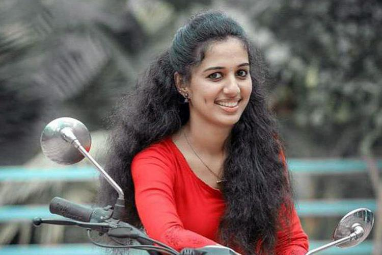Vismaya wearing a red top with her hair let loose on a motorbike