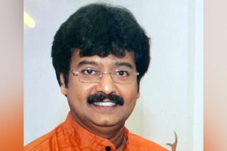 Actor Vivek in an orange shirt. Younger face.