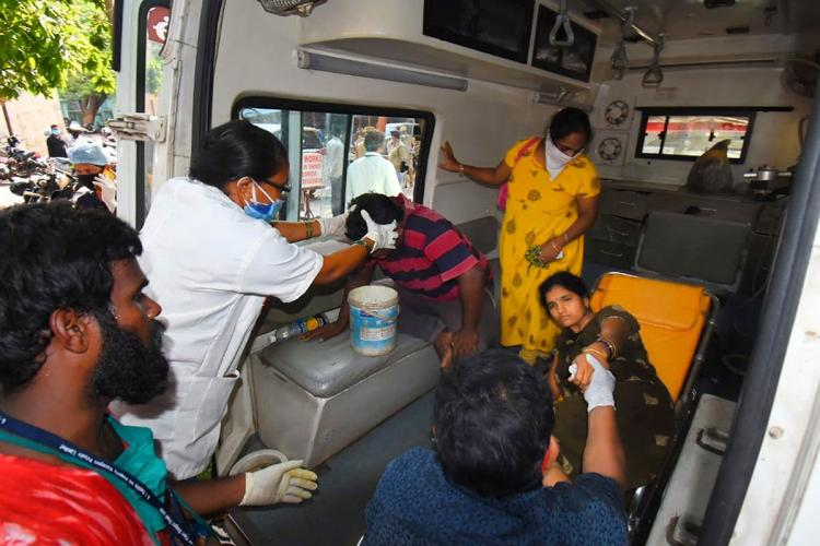 A woman and a man being hauled into an ambulance in the aftermath of the Vizag gas leak