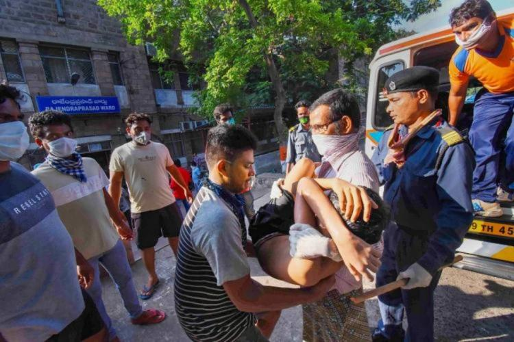 A boy affected by the Vizag gas leak being rescued by people surrounding him and carrying him into an ambulance