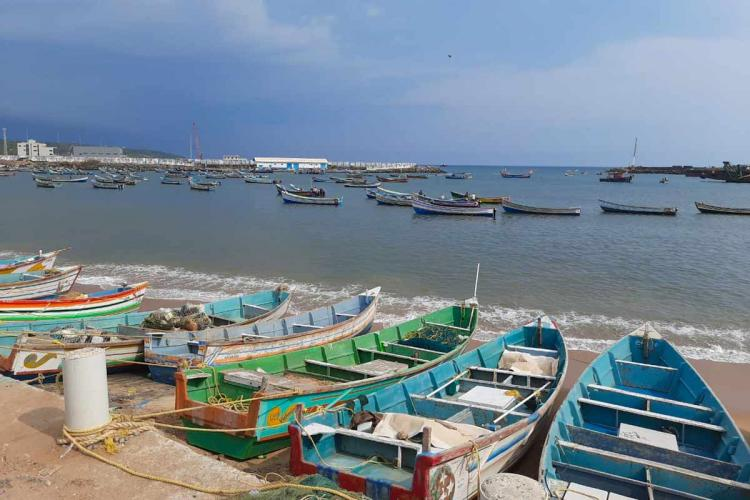 Colourful boats lined up on the shore against the blue sea and clear blue sky