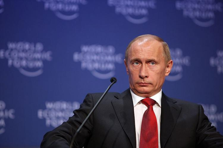 File photo of Vladmir Putin shows him at an event wearing a black suit and a red tie