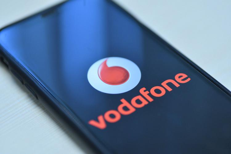 The logo of Vodafone in red on the display of a smartphone