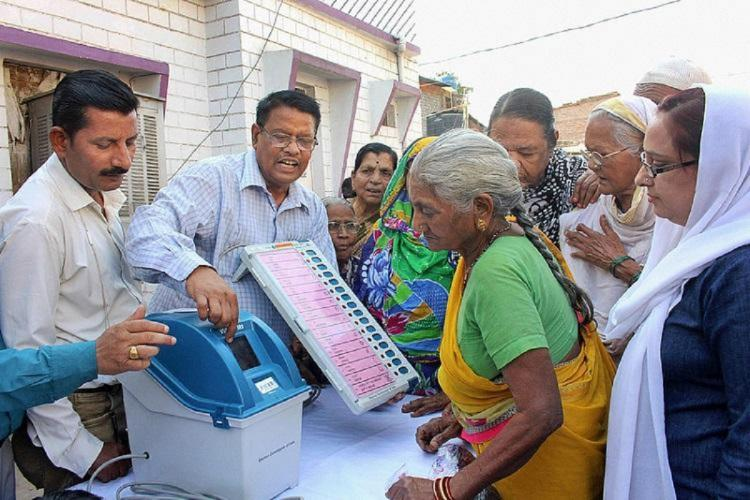 EC officials explaining the EVM machine and voting process to a senior citizen