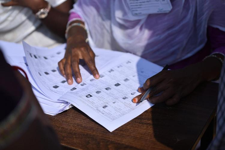 An official at a polling booth checking voters list