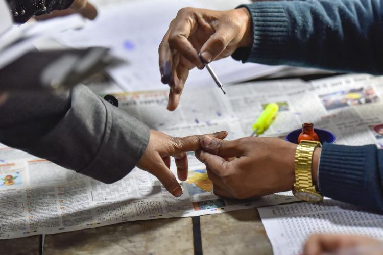 An election official applies ink on the finger of a citizen after he casts his vote in an election in India