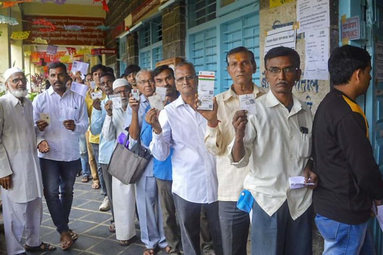 People queue up to cast their votes in an election in India Many of them hold up their voter ID cards towards the camera