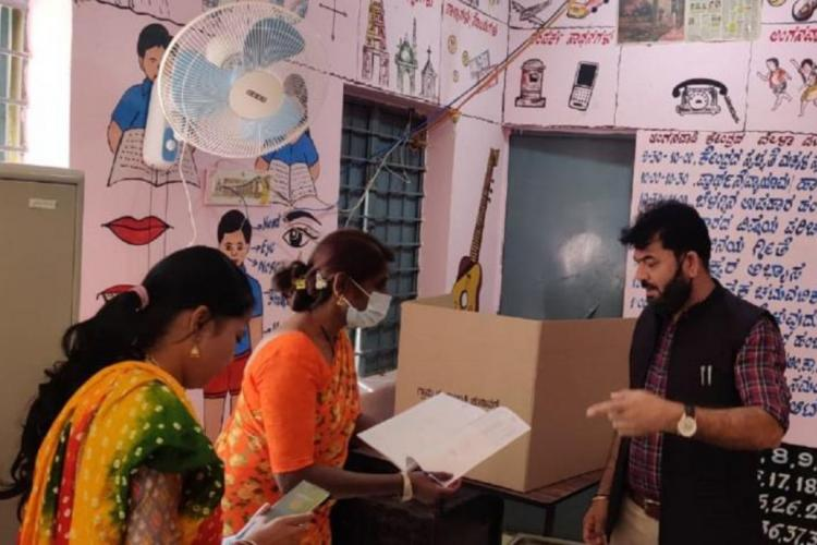 Polling officers guiding a voter