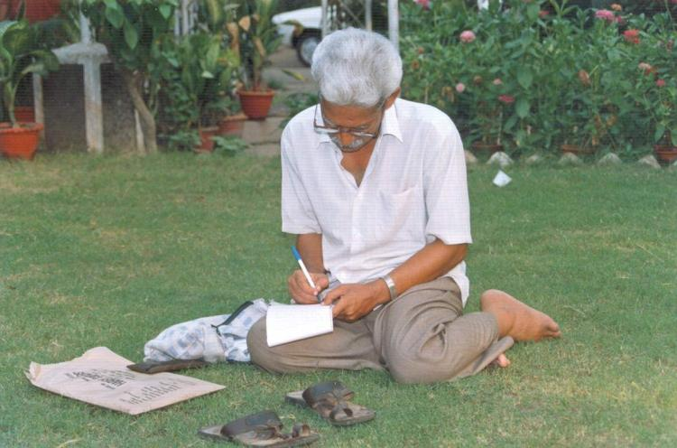 Telangana Poet Varavara Rao writing something by sitting on a green grass