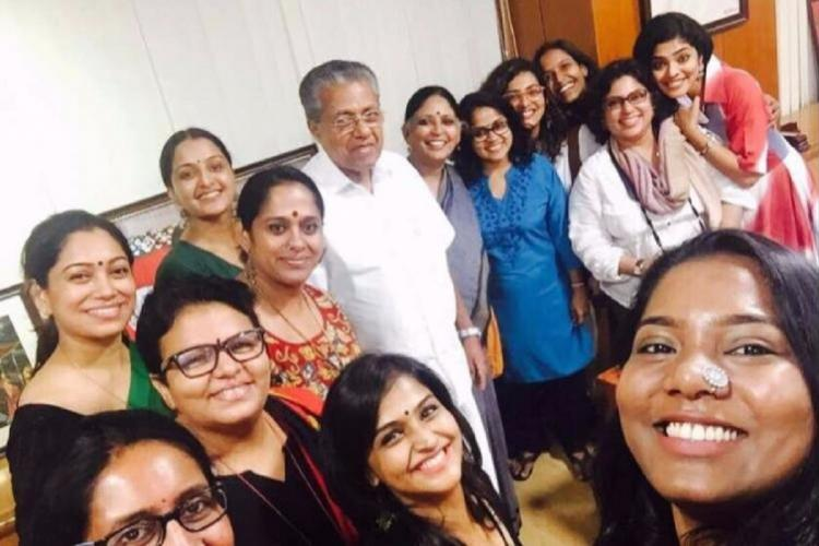 A number of women -- members of WCC -- stand around CM Pinarayi for a selfie