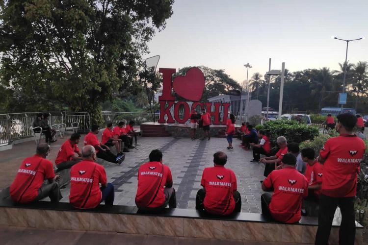 Members of the Walkmates Pachalam club in Kochi dressed in red uniforms sitting around outdoors engaged in a game