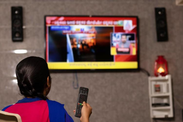 A woman is chaning the TV channel with remote