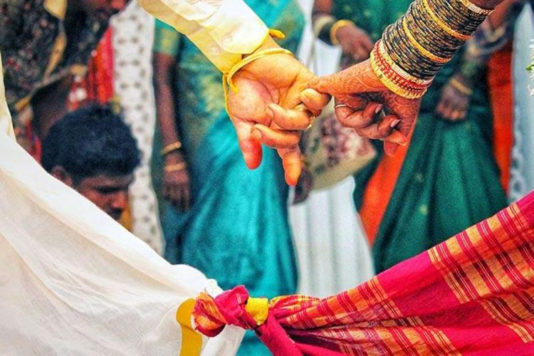 A wedding picture in which a couple were seen holding thier hands in a wedding attire amid relatives