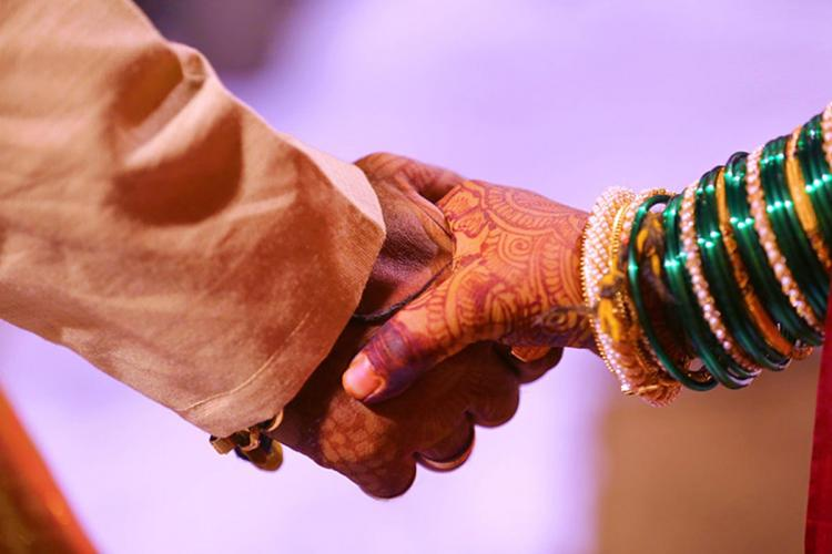 Bride and groom holding hands Only hands are highlighted in the photo The brides is wearing green bangles on the hand and has mehandi