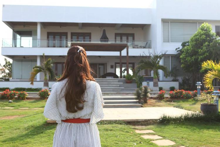 A woman in a white dress stands in front of a big house