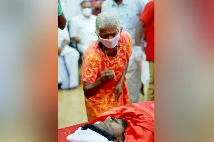 An elderly woman in an orange nightie looks down at the dead body of Sanoop wearing a mask