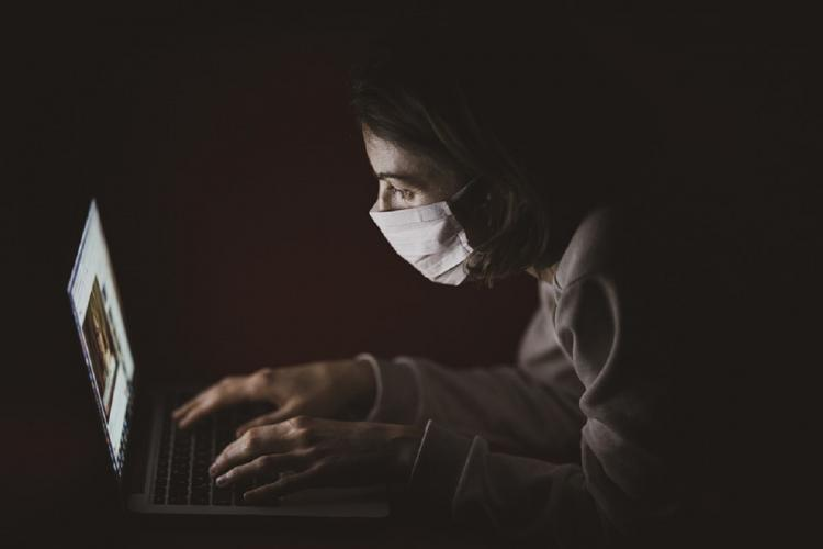 Woman wearing mask working on a laptop face only lit by light from laptop