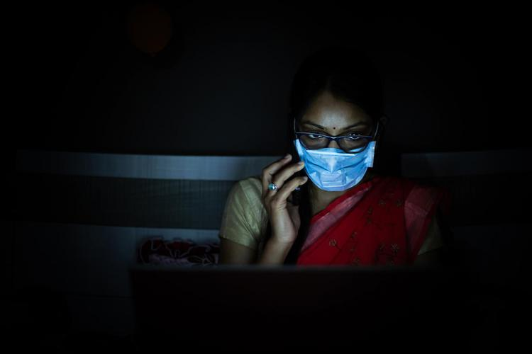 Woman wearing a red saree and mask working on laptop