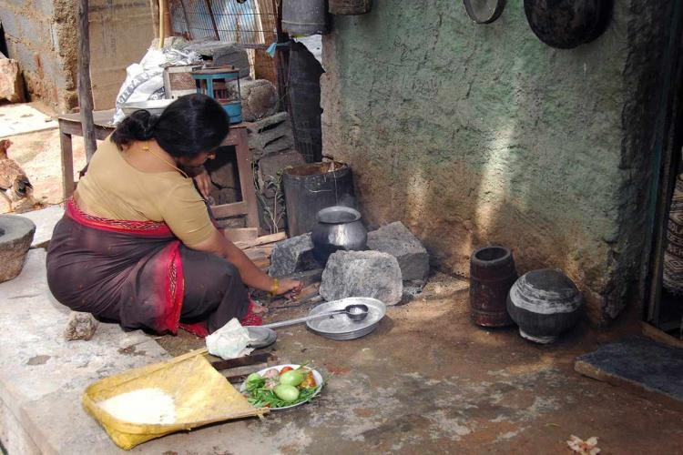 woman turned away from the camera cooking wearing a brown and red saree