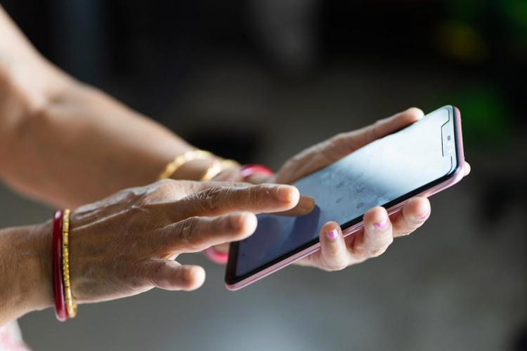 A womans hand touching the screen of a smartphone there are two bangles on each hand