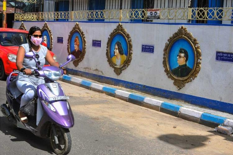 Woman riding a bike along a road with colourful murals on the wall The woman has a face mask on her face and also wears a sunglass