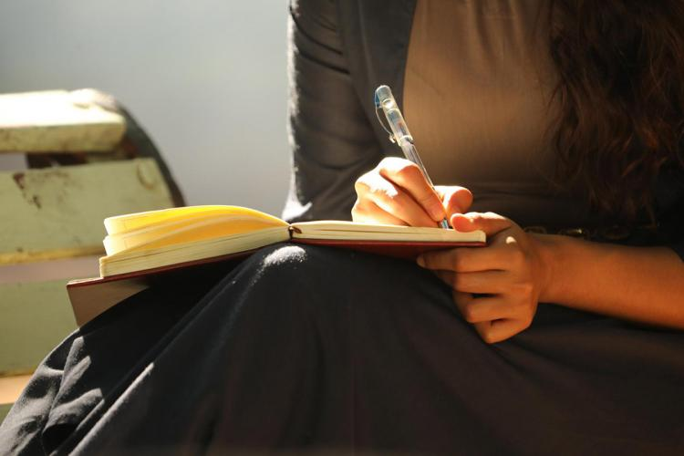 A woman from shoulder down with a pen in her right hand writing in a book