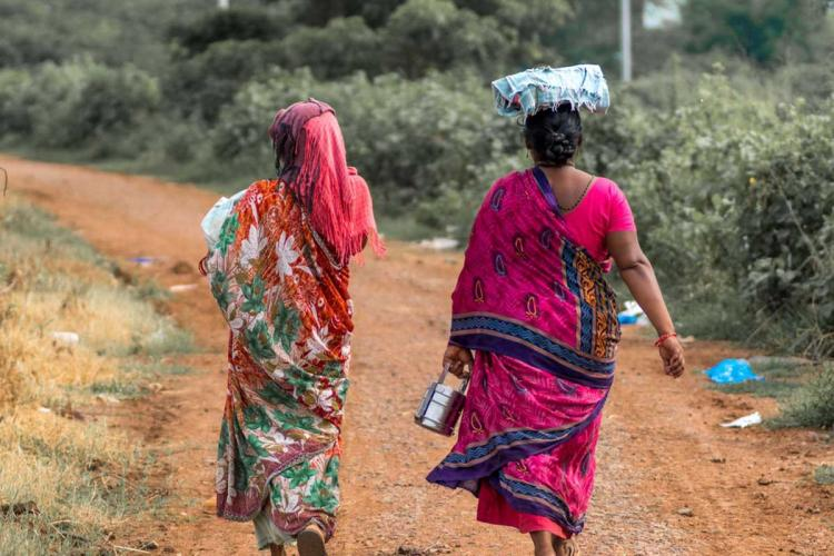A photo of two saree-clad women walking on a mud road shot from the back