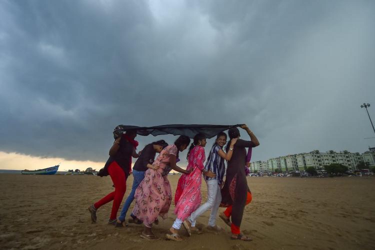 Youngsters take a walk along Marina Beach as dark clouds gather in the sky in Chennai