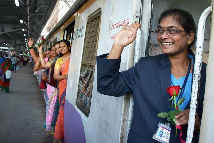 Women passengers wave from suburban train in Mumbai
