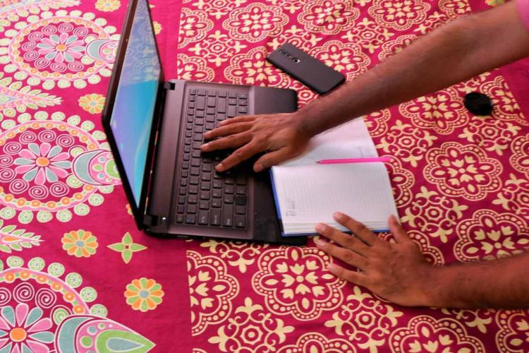 A person working from home on a laptop with a notebook and mobile on the side with the laptop placed on a red bright bedsheet
