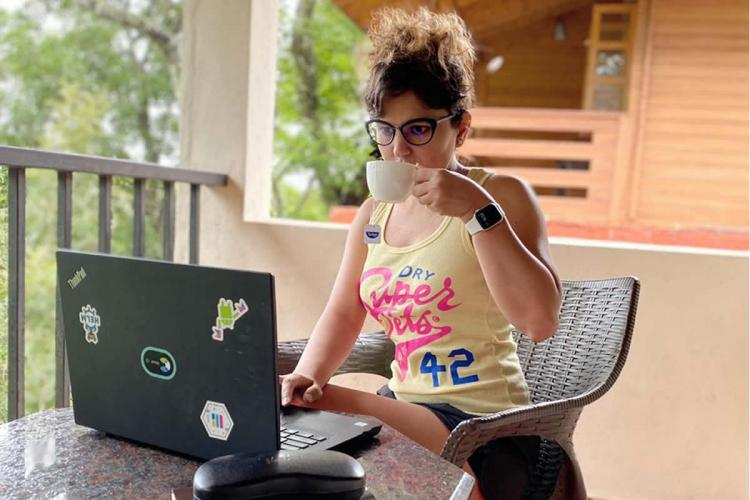A young woman sitting on a balcony sipping a cup of tea with a laptop open in front of her Representative image for a workation