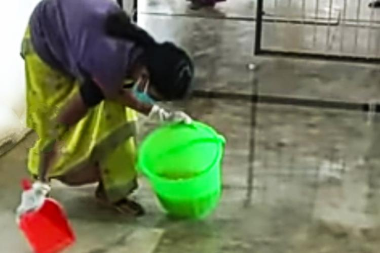 A worker cleaning the stagnant water in the dialysis unit of Tiruvarur Government Hospital