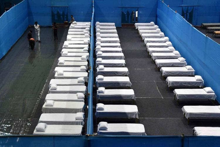 three rows of beds are visible at a quarantine facility as a worker arranges things before the centre is open