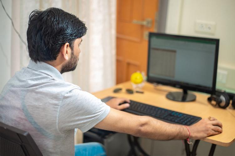 Man sitting at a desktop at home, working