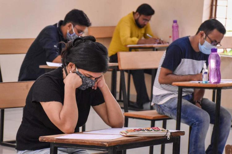 Students in masks writing exam
