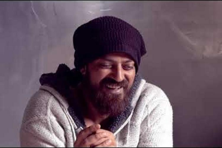 Xuhaib in white sweatshirt and dark balaclava and brown beard laughs