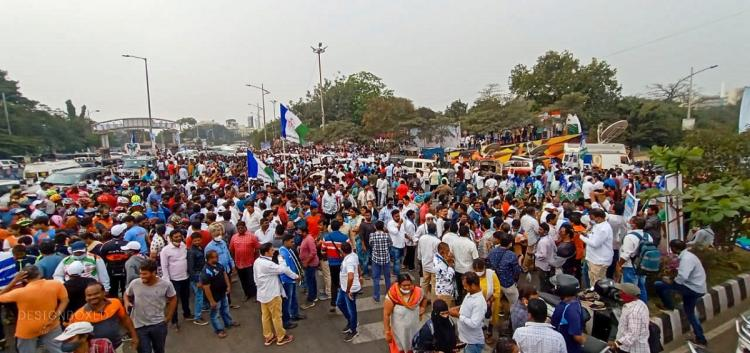 Scores of people can be seen walking on the road in protest against privatisation of Vishakapatnam steel plant