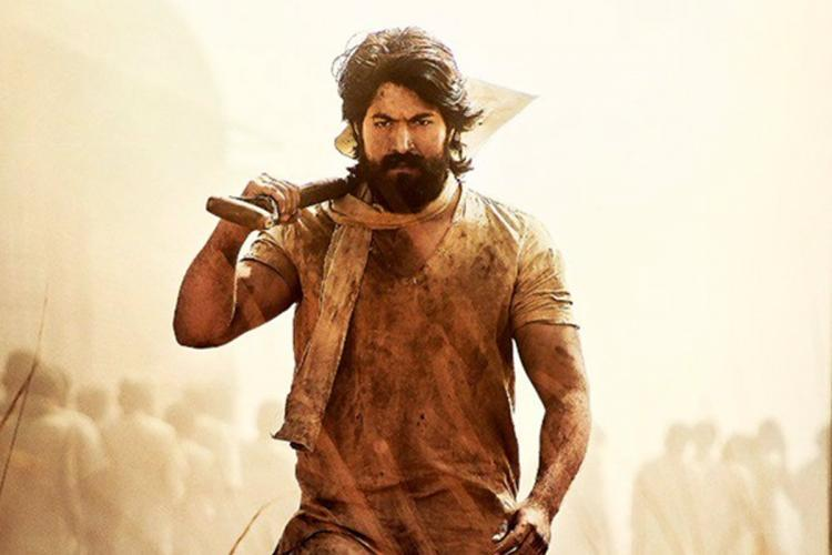 Actor Yash in KGF wearing dusty clothes and a cloth around his neck and carrying a spade on his right shoulder