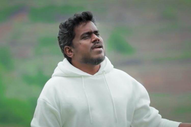 Yuvan Shankar Raja is seen singing in the backdrop of trees in the image