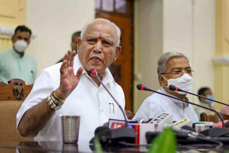 Karnataka CM BS Yediyurappa in an earlier meeting with officials speaking into the mic