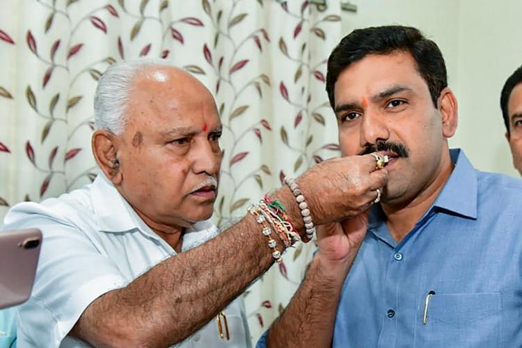 BS Yediyurappa hand feeding a sweet to his son BY Vijayendra