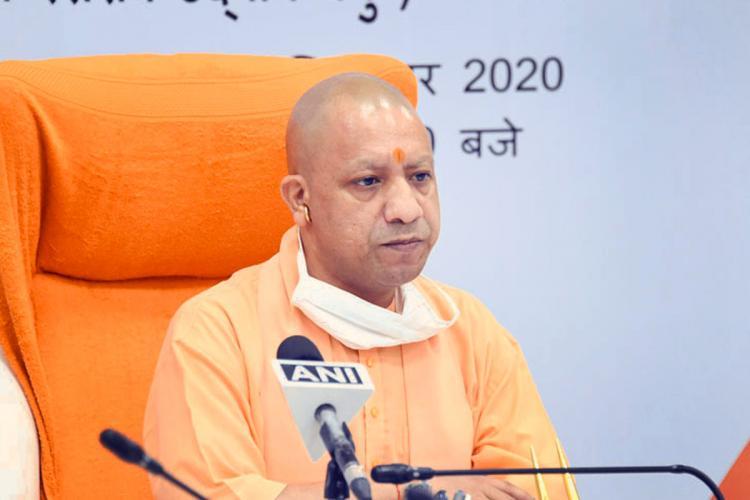 Uttar Pradesh Chief Minister Yogi Adityanath sitting on a saffron coloured chair