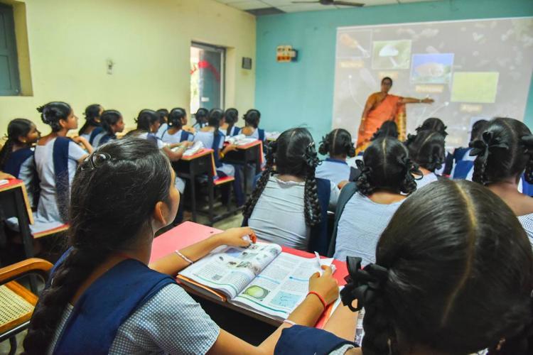 Representative image of girls in school uniform attending a class inside a classroom