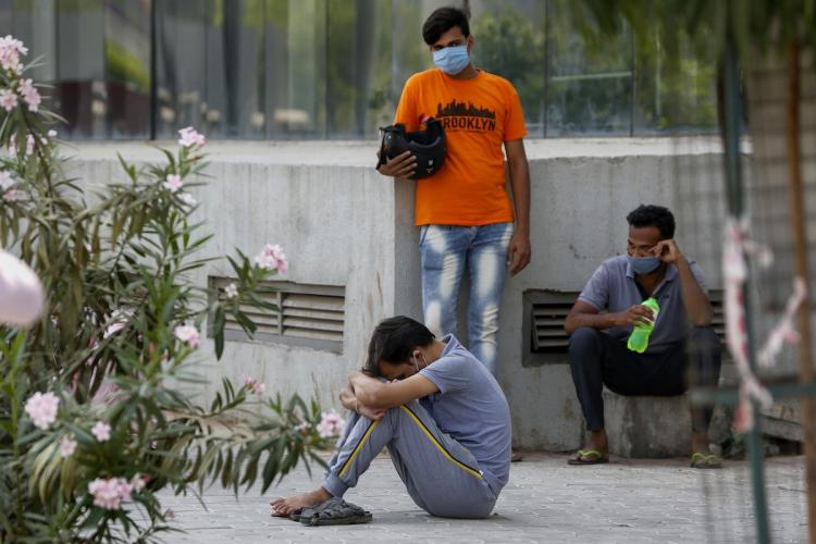 Three young men one sits with his head bowed one stands behind in an orange shirt wearing a mask and a third sits on a platform holding a bottle of water