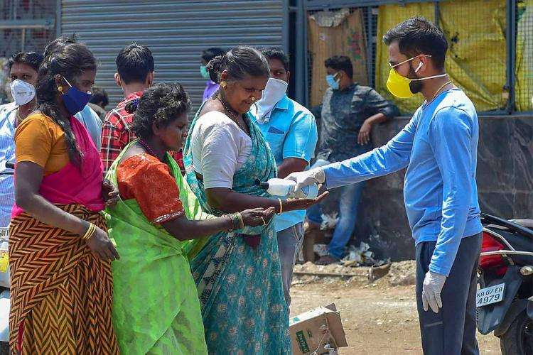 A youth distributing COVID-19 relief materials to women who have queued
