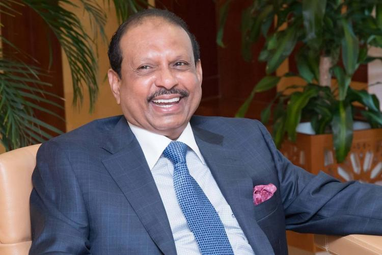 Chairman and Managing Director of Abu Dhabi-based LuLu Group Yusuffali in blue suit smiles sitting on couch